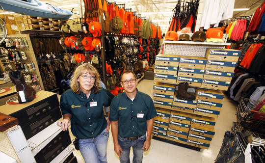 Runnings store manager Dennis Dosch, center, and assistant manager Karla Whiting, left, in the sporting goods department of the Aberdeen store.