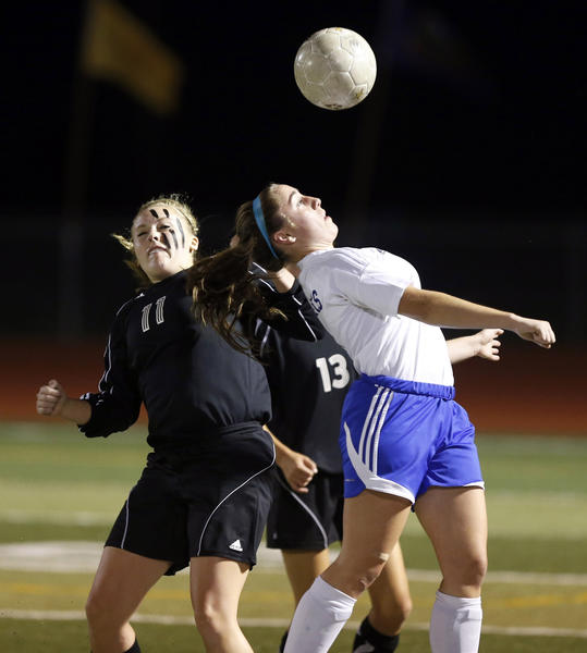 Sioux Falls O'Gorman's Kylie Lamberty, right, gets to the ball ahead of Groton Area's Regan Lewandowski, left, during their game Thursday night at the State Soccer Tournament.