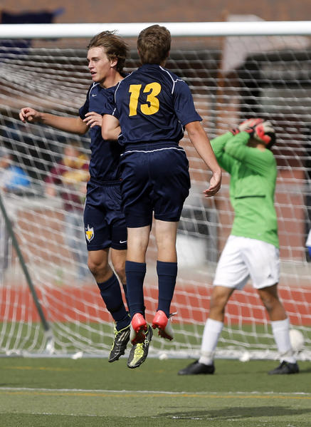 Tea Area's Tarin Smallfield, left, celebrates with teammate Jordan Fechner (13) after scoring a goal on Sioux Falls Christian goal keeper Tim Hustrulid, far right, during the first overtime period of Thursday's match at the State Soccer Tournament at Swisher Field.