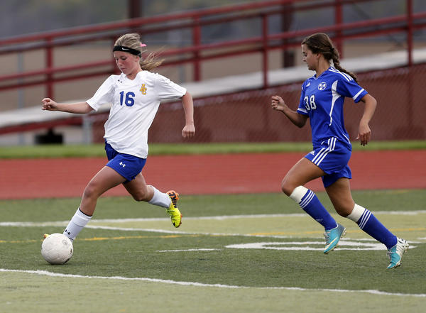 Aberdeen Central's Taylor Morgan, left, pushes the ball up field past St. Thomas More's Kassidy Kirsch, right, during their game Thursday at the State Soccer Tournament. Morgan went on to score on the play.