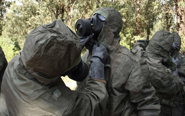 Members of the Tunisian military adjust each other's protective gear as they take part in an exercise simulating a nuclear attack in 2010. Special units from 11 countries took part in the exercise by the Organization for the Prohibition of Chemical Weapons.