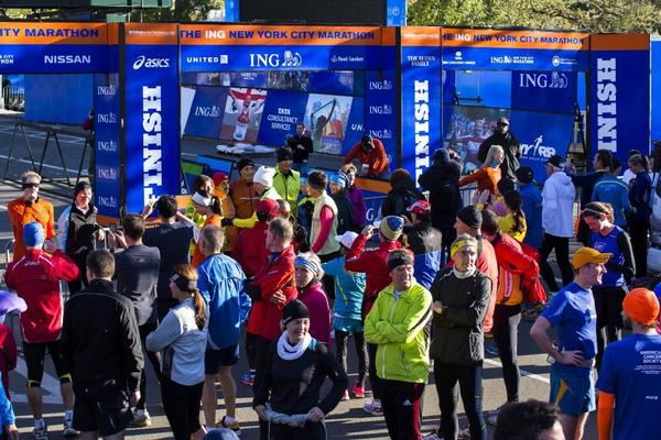 A crowd of runners stands near the barricaded Central Park finish line for the canceled New York City Marathon