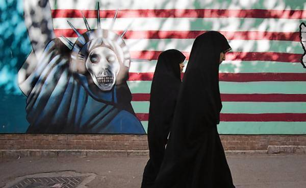 Iranian women walk past an anti-American mural on the wall of the former U.S. embassy in Tehran.