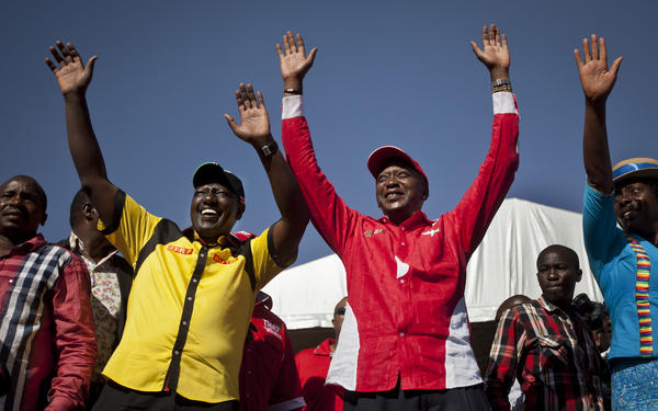 Then- Kenyan presidential candidate Uhuru Kenyatta, center right, and his running mate William Ruto, center left, greet the crowd as they arrive at the final election rally of Kenyatta's The National Alliance party at Uhuru Park in Nairobi in March.