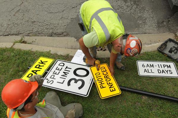 Workers prepare signs in the 5200 block of W. Foster Ave. alerting motorists that speed cameras are in place.