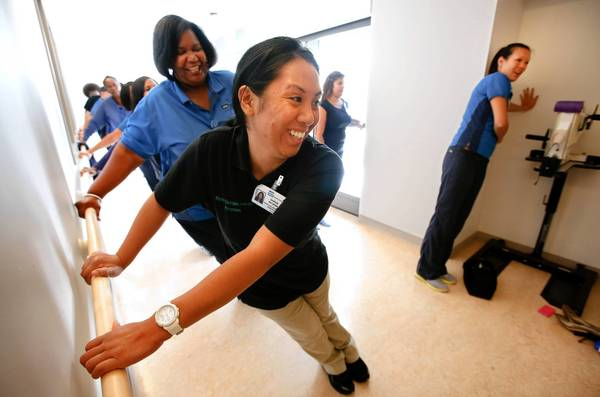 Sharon Batarina, a physcial therapy assistant, foreground, is joined by other staff members of UCLA Health in a Bruin Break workout at Ronald Reagan UCLA Medical Center in Westwood.