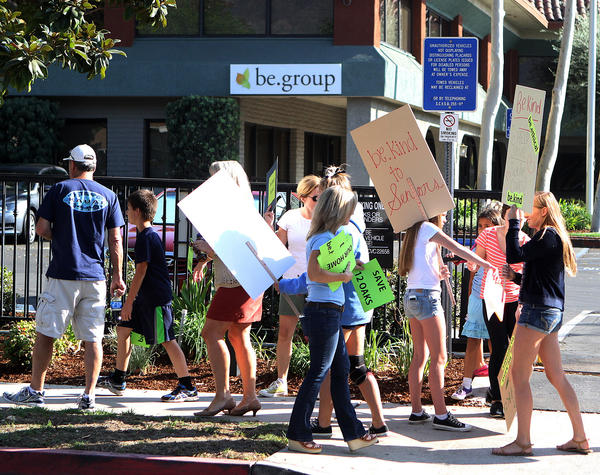Protesters gather and begin to walk in protest in front of be.group in Glendale, protesting the closing of 12 Oaks Lodge in La Crescenta on Wednesday, October 2, 2013. Nearly 125 people protested in front of the Glendale business.