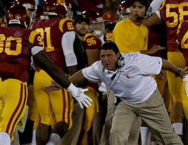 USC interim coach Ed Orgeron congratulates his team during a game against Arizona on Thursday.