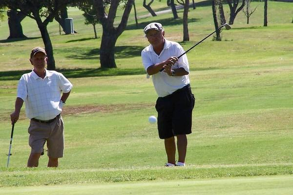 Roberto Jara, center, chips onto the fourth green at Costa Mesa Country Club's Los Lagos course during the 10th Boys & Girls Club of the Harbor Area Westside branch golf tournament Monday. Jara joined the public club's men's group in the '60s. Jara's friend, Vito Vento, looks on.