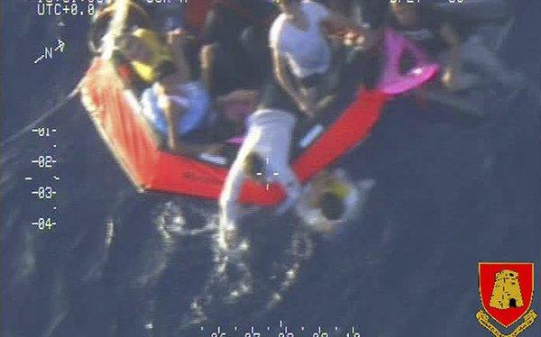 An image released by the Maltese army shows migrants on a life raft after their ship capsized Friday.