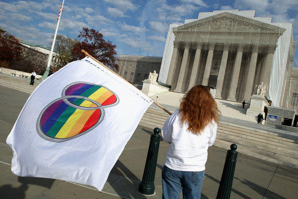 Same-sex marriage proponent Kat McGuckin of Oaklyn, New Jersey, holds a gay marriage pride flag while standing in front of the Supreme Court in Washington, DC.