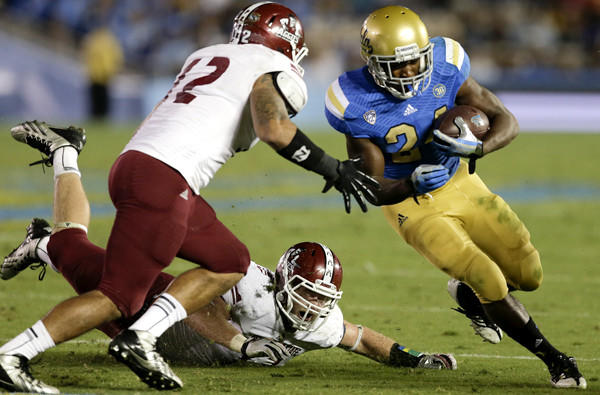 UCLA running back Paul Perkins gets past New Mexico State linebacker Bryan Bonilla as safety Tre Wilcoxen moves in for the tackle during a game earlier this season.