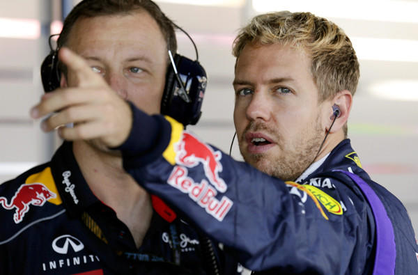 Formula One driver Sebastian Vettel, right, talks with a crew member before a practice session of the Japanese Grand Prix in Suzuka, Japan.