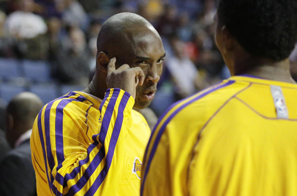 Lakers guard Kobe Bryant talks to teammate Nick Young before a preseason game against the Denver Nuggets on Tuesday. Bryant has not played as he continued to rehabilitate his surgically repaired left Achilles' tendon.