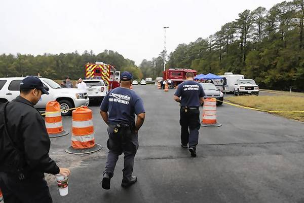Emergency and search and rescue personnel gather at a command post at the entrance to the Great Dismal Swamp canal trail where they are searching for a possible missing plane, Friday, October 11th, 2013.