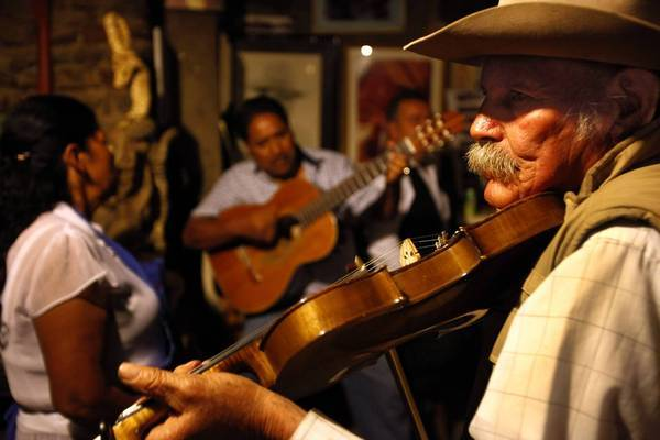 Don Heriberto Aguilar, right, plays violin at Rancho El Tule, his winery in the mountains above Ensenada in Baja California.