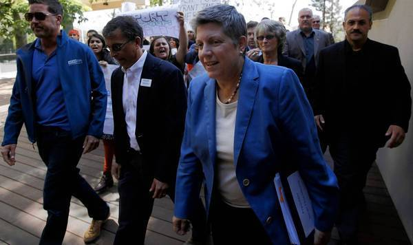 New UC President Janet Napolitano, center, walks past a group of protesters Friday on her way into a lunch with student leaders during her first official visit to UCLA.