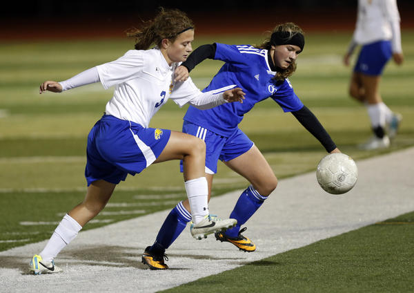 Aberdeen Central's Rachel Hagen, left and Sioux Falls O'Gorman's Izzy Hedge, right, go after the ball during Friday's championship game at the South Dakota State Soccer Tournament at Swisher Field. photo by john davis taken 10/11/2013