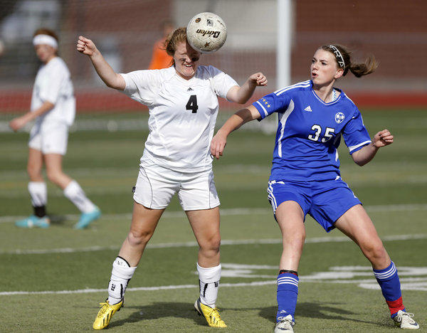Groton Area's Emiy Locke, left, gets her head on the ball as St. Thomas More's Ciara Duffy, right, looks on during Friday's third place game at the South Dakota State Soccer Tournament at Swisher Field. photo by john davis taken 10/11/2013