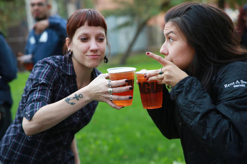 K.L. Kenzie, left, and Maegen Cadena toast each other as the Lagunitas Brewing Company prepared a Happy Hour gathering on Oct. 11. Brewing company officials worry that the shutdown may delay its seasonal beers.