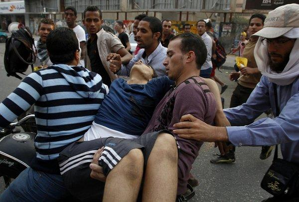 Supporters of ousted Egyptian President Mohamed Morsi carry an injured comrade in Cairo's eastern Nasr City district on Friday after clashes broke out during a demonstration against the military.