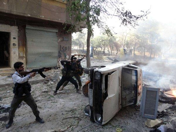 Rebel fighters open fire from behind a car during clashes in the the northern Syrian city of Aleppo on Wednesday.