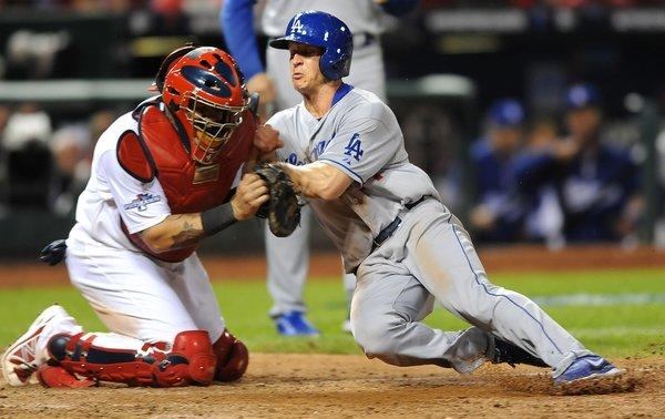 Cardinals catcher Yadier Molina braces for the collision, and appears to fail to apply the tag, as Dodgers second baseman Mark Ellis tries to score on a flyout by Michael Young in the 10th inning of Game 1.