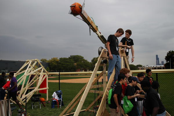 "The ""Mach 1"" team stands on their robotic pumpkin launcher for the ninth annual Pumpkin Launch at the Illinois Institute of Technology Ed Glancey Baseball Field on Saturday, Oct. 12, 2013 in Chicago. ""Mach 1"" was able to launch their pumpkin through a program on a computer."