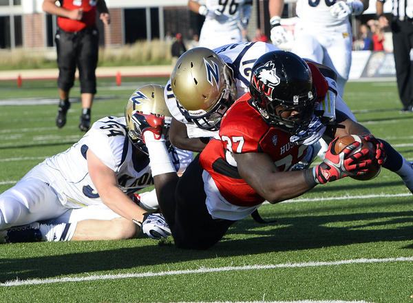Huskies tight end Desroy Maxwell dives for the touchdown against Akron's Bill Alexander and linebacker Dylan Evans during the first quarter.