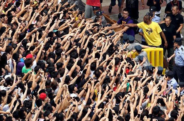 Kobe Bryant (yellow shirt) had plenty of hands to shake during a visit to China last year.