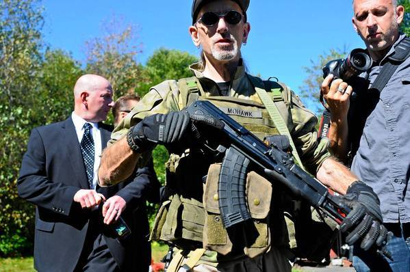 An armed supporter walks ahead of Gilberton Police Chief Mark Kessler, background left, as he makes his way back into a closed disciplinary hearing.
