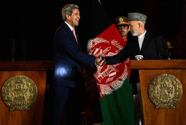 U.S. Secretary of State John F. Kerry greets Afghan President Hamid Karzai during their joint news conference after their talks in Kabul, the Afghan capital.