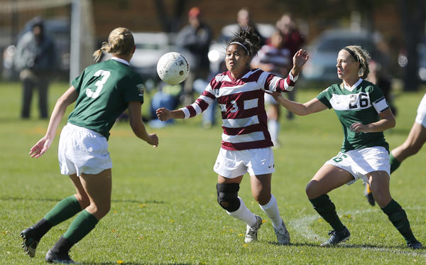 Northern State University's Khachirha Tugas, center, goes after the ball between Bemidji State's Abigail Nyquist, left and Samantha Lumbert, right, during the first half of Saturday's game at Jerde Field. photo by john davis taken 10/12/2013