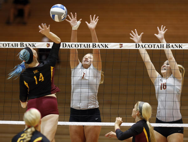 Northern State University's Cari McGarvie, center, and Macey Finizio, right, defend the net as University of Minnesota-Crookston's Katie Miedtke, left, reaches to hit the ball during Saturday night's match at Wachs Arena. photo by john davis taken 10/12/2013