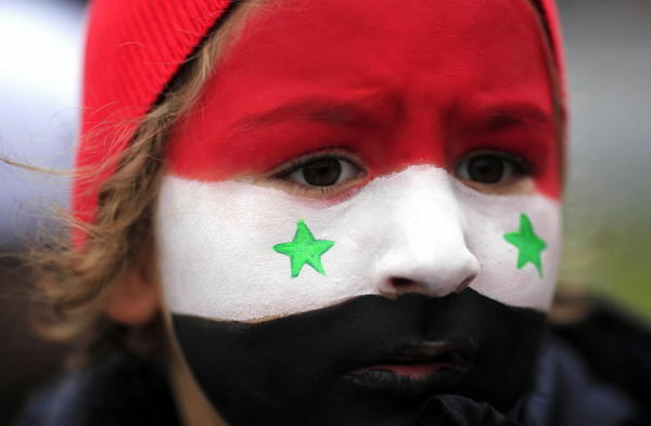 A girl, with her face painted in the colors of the Syrian flag, attends a demonstration by members of the Syrian community in Romania, organized by the European Front of Solidarity for Syria, in Bucharest October 13, 2013.