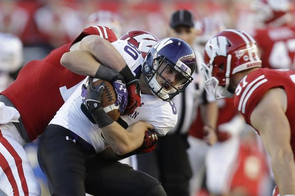 Mike Jensen #80 of the Northwestern Wildcats makes the catch before getting tackled by Tanner McEvoy #17 of the Wisconsin Badgers.