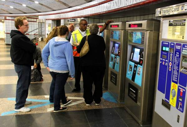 CTA customer service assistant Alton Jackson (yellow vest) explains the Ventra fare card system to riders at the Red Line station at Grand Avenue and State Street.