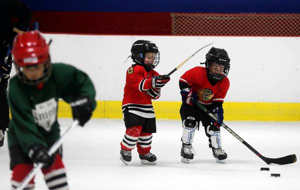 Daniel Fiorentino, 4, center, and Mike Scheerin, 4, right, go for the puck at an ice hockey class last week at Southwest Ice Arena in Crestwood.