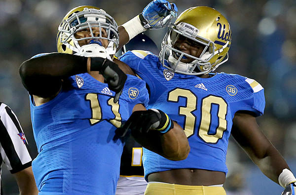 UCLA linebacker Anthony Barr, left, celebrates with teammate Myles Jack after recording a sack during the first quarter of Saturday's game.
