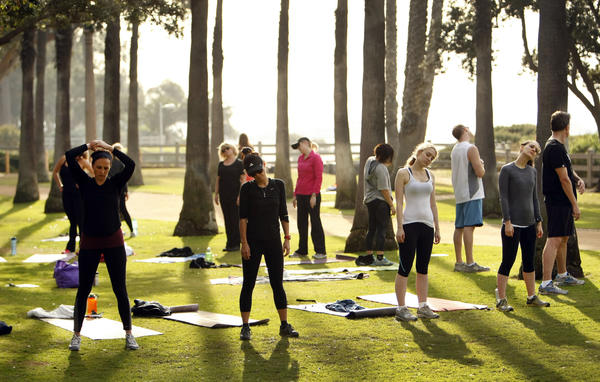 Students stretch at the conclusion of a fitness class workout at Palisades Park in Santa Monica in January. The City Council has recently set restrictions on and established fees for the use of public parks for training.