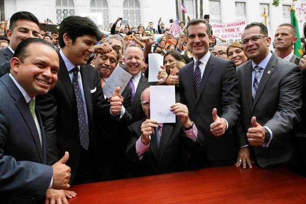 Assmblyman Luis Alejo, left, Sen. Ricardo Lara, Sen. Kevin de Leon, Los Angeles City Councilman Gil Cedillo, Senate President Pro Tem Darrell Steinberg, Los Angeles Mayor Eric Garcetti and Assemblyman Manuel Perez give the thumbs up as Gov. Jerry Brown signs a bill allowing people in the U.S. illegally to obtain California driver's licenses.