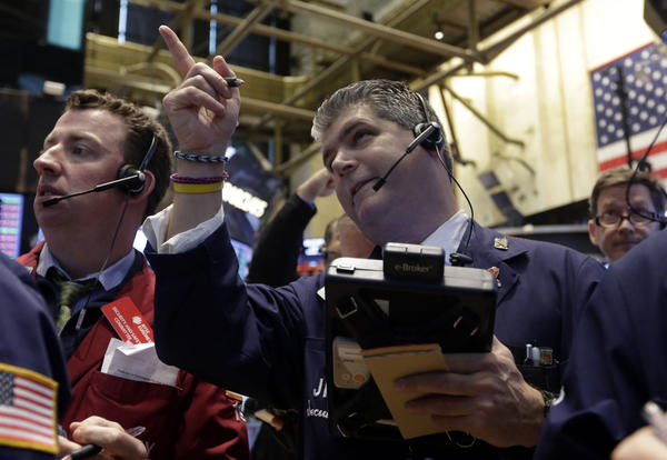 Trader John Panin, center, works on the floor of the New York Stock Exchange on Friday.