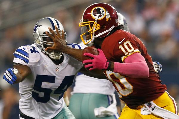 Robert Griffin III scrambles with the ball against Bruce Carter of the Cowboys on Sunday.