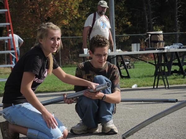 Boyne Falls junior, Kaylee Herman, 16 and senior, Clifford Baker, 17, help construct a hoop house at Boyne Falls Schools, Friday, Oct. 11, 2013.
