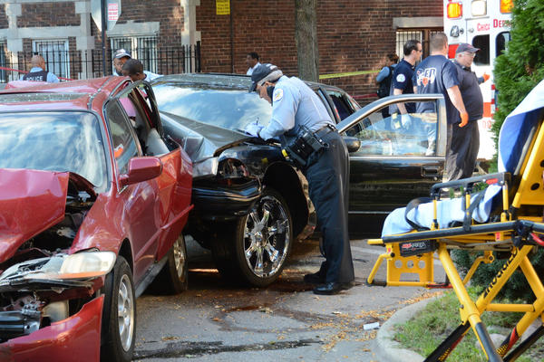 Paramedics take a man who has been shot from an auto at 82nd Street and Drexel Boulevard in Chicago. One person was killed and another wounded in shootings a block apart in the East Chatham neighborhood on the South Side this morning, police said.