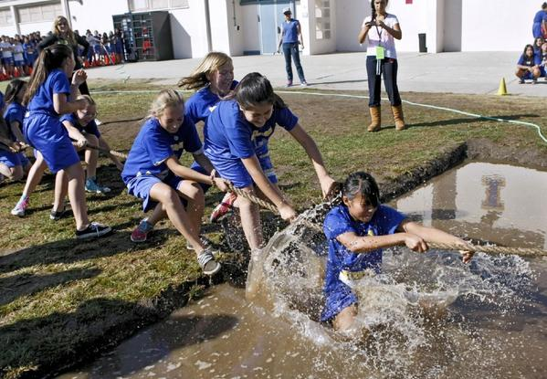 A team of seventh grade girls are pulled into muddy waters as their team looses a tug-of-war heat at Wilson Middle Schoo