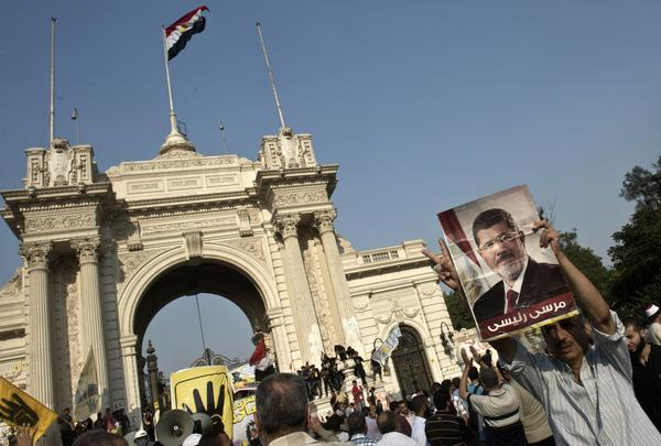 A supporter of Egypt's Muslim Brotherhood movement holds a poster of ousted President Mohamed Morsi at a rally Friday outside the presidential palace in Cairo.