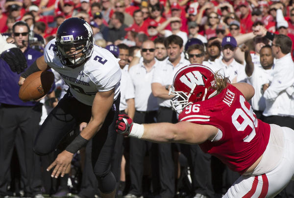 Northwestern Wildcats quarterback Kain Colter avoids Wisconsin Badgers nose tackle Beau Allen during the first quarter at Camp Randall Stadium.