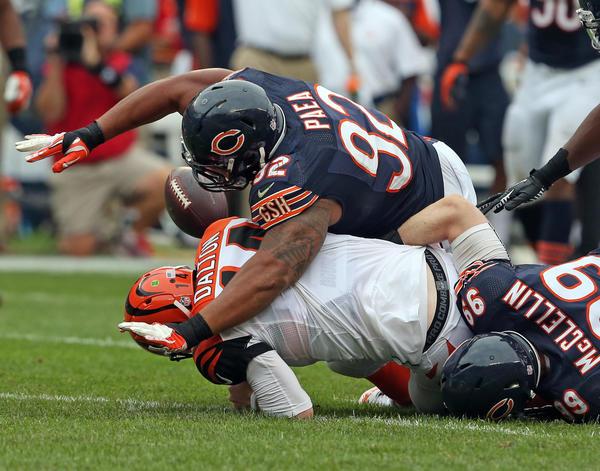 Bears defensive tackle Stephen Paea (92) and defensive end Shea McClellin (99) bring down Bengals quarterback Andy Dalton.