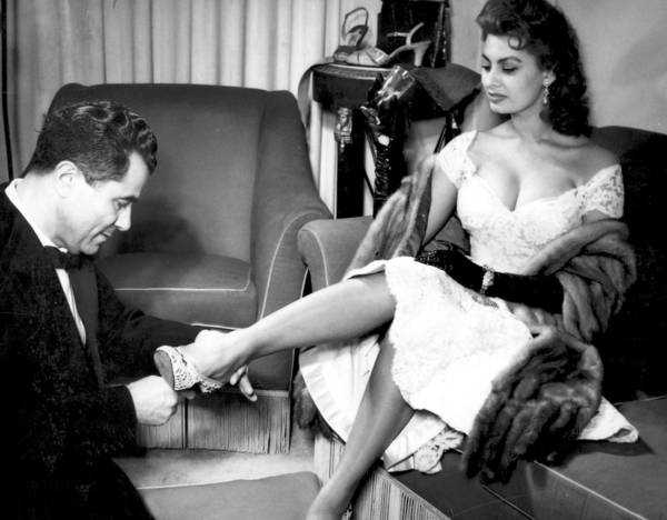 Salvatore Ferragamo with Sofia Loren as she tries on a sandal of Tavarnelle lace, 1955.